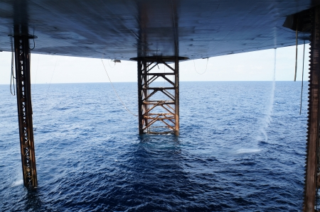 Underneath Jack Up Drilling Rig In The Ocean - Oil and Gas Industry Stock Photo