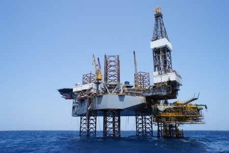 Offshore Jack Up Drilling Rig and The Production Platform in The Middle of The Sea Stock Photo