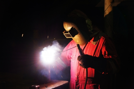 skilled labour: Welder uses torch to make sparks to weld metal equipment.