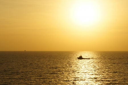 construction crew: Offshore Boat for Crew Change Before Sunset With Stunning Golden Sky Stock Photo