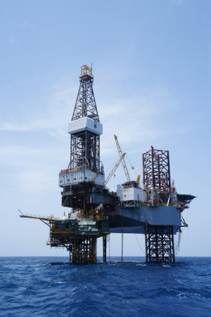 sun oil: Offshore Jack Up Drilling Rig Over The Production Platform Stock Photo