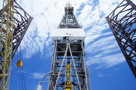 driller: Front View of Derrick of Offshore Oil Drilling Rig and Rig Legs on Sunny Day           Stock Photo