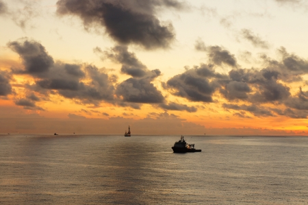 Supply boat and offshore drilling rig in the middle of the ocean in the evening time