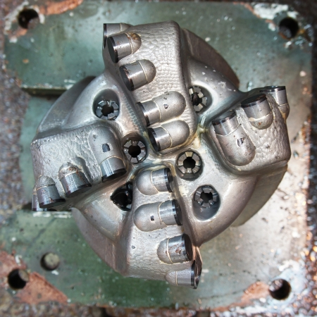 Damaged PDC drilling bit just pulled out of hole      Stock Photo