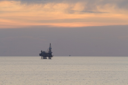 Jack up rig in the middle of the sea at sun set time photo