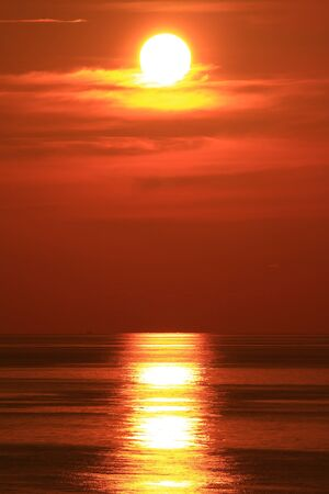 horizon reflection: Dramatic Sun Set With Big Red Sun in The Middle of The Ocean Stock Photo