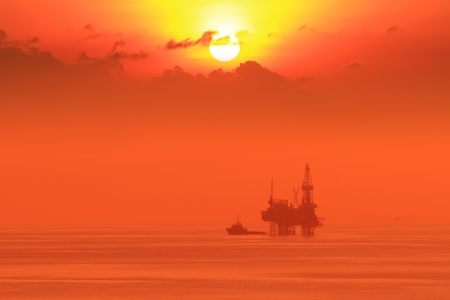 jack up: Silhouette Offshore Jack Up Drilling Rig and Boat At Sun Set Time (Yellow Tone)