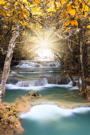 Autumn deep forest waterfall with light beam in Kanchanaburi, Thailand