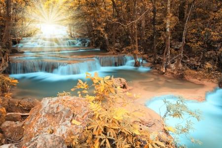Autumn deep forest waterfall with light beam in Kanchanaburi, Thailand