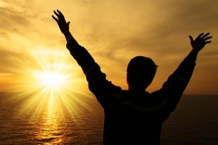 Silhouette immagine di uomo alzando le mani con raggio di luce