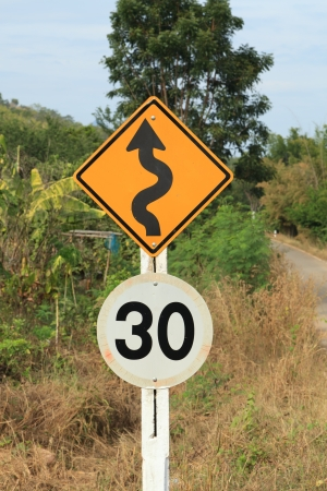 Zig Zag road warning sign and 30km limit speed limit sign in country side