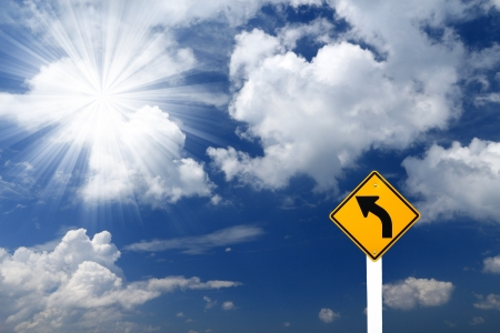 Direction sign- left turn sign pointing to rays of light on blue sky background Stock Photo