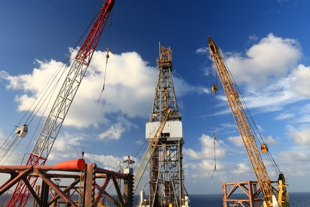 Jack Up Offshore Drilling Rig With Rig Cranes on Sunny Day in The Middle of Ocean
