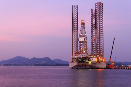jack up: Jack up oil drilling rig in the shipyard at sunset time Stock Photo