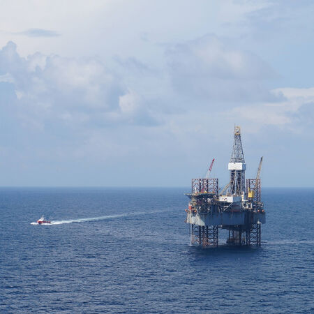 jack up: Jack up oil drilling rig and a crew boat in the middle of the ocean       Stock Photo