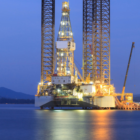 Jack up oil drilling rig in the shipyard for maintenance at sunset time Stock Photo