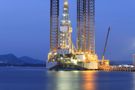 driller: Jack up oil drilling rig in the shipyard for maintenance at sunset time Stock Photo