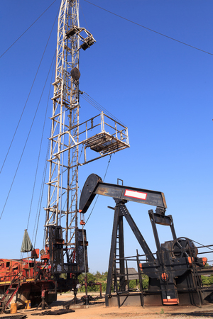 beam pump: Oil Pump Jack (Sucker Rod Beam) and Workover Rig on Sunny Day