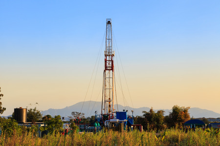 worksite: Oil Land Drilling Rig Working In The Field For Petroleum Exporation at Sunset Time Stock Photo