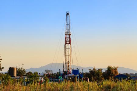 pozo petrolero: Tierra de la perforación petrolífera Rig trabajan en el campo del petróleo Exporation en Sunset Time