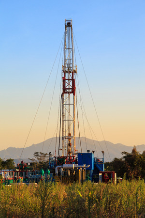upstream: Oil Land Drilling Rig Working In The Field For Petroleum Exporation at Sunset Time Editorial