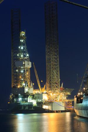 pozo petrolero: Levantar la plataforma de perforación petrolera en el astillero en la noche