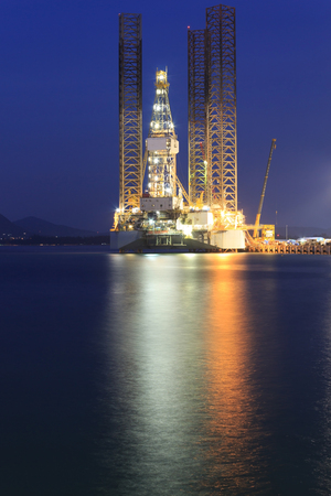 well platform: Jack up oil drilling rig in the shipyard for maintenance at sunset time Stock Photo