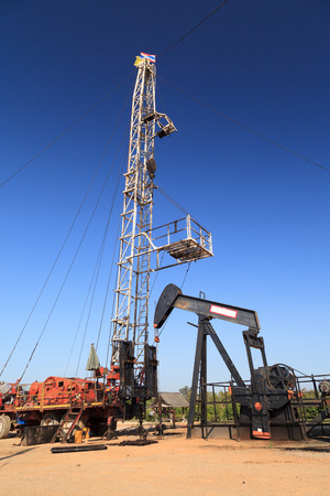 nodding: Oil Pump Jack (Sucker Rod Beam) and Workover Rig Working on Oil Well on Sunny Day