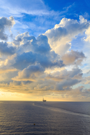 oil platforms: Offshore jack up drilling rig in the middle of the ocean during sunset time