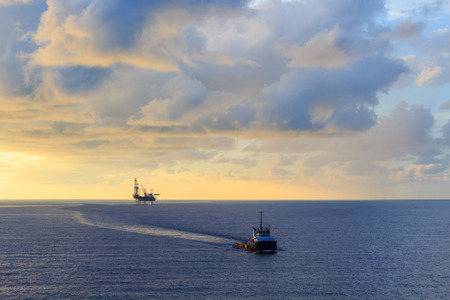 Offshore jack up drilling rig and supply boat in the middle of the ocean during sunset time photo