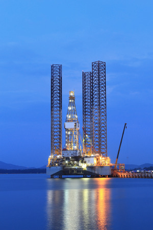 oilrig: Jack up oil drilling rig in the shipyard for maintenance at sunset time Stock Photo