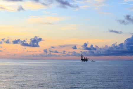 pozo petrolero: Levantar la plataforma de perforación en alta mar en el medio del océano durante el tiempo de la puesta del sol Foto de archivo