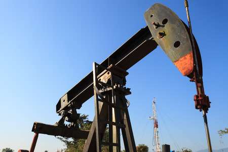 nodding: Sucker Rod Beam (Oil Pump Jack) and Drilling Rig Stock Photo