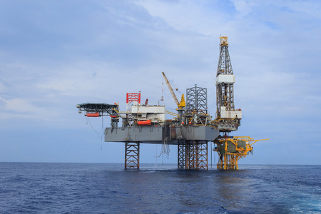 jack up: Offshore Jack Up Drilling Rig Over The Production Platform in The Middle of The Sea - View from Crew Boat Editorial