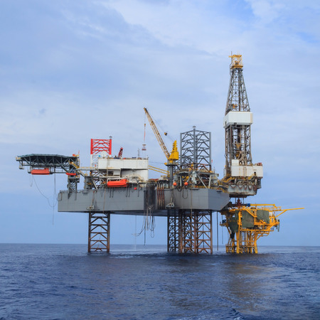jack up: Offshore Jack Up Drilling Rig Over The Production Platform in The Middle of The Sea - View from Crew Boat Stock Photo