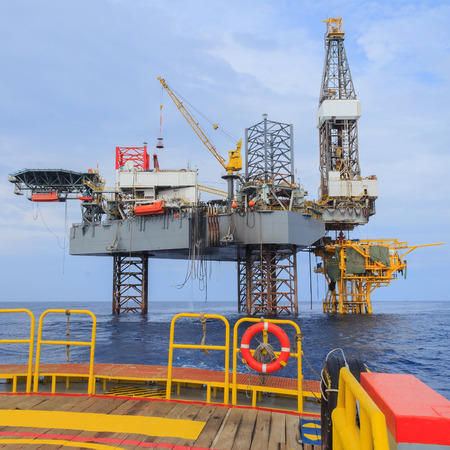 offshore jack up rig: Offshore Jack Up Drilling Rig Over The Production Platform in The Middle of The Sea - View from Crew Boat Stock Photo