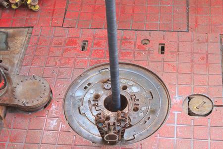 pozo petrolero: Resbal�n en la mesa giratoria, mientras que los pozos de petr�leo de perforaci�n y tuber�a que est� siendo rotados - Top View