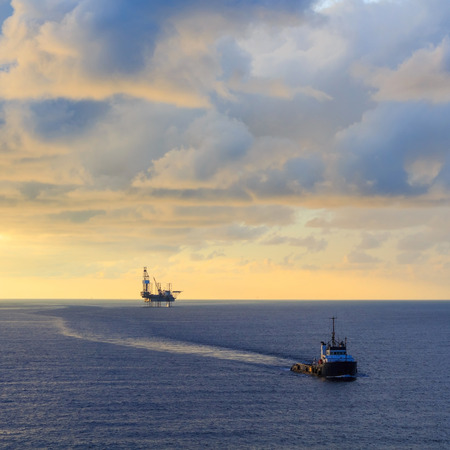jack up: Offshore jack up drilling rig and supply boat in the middle of the ocean during sunset time