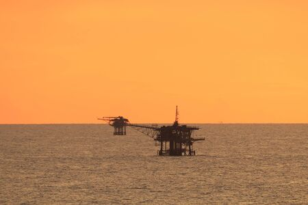 petroluem: Offshore platform in the middle of the ocean with beautiful sunset