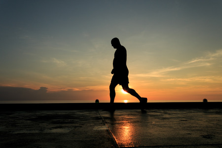 helideck: Silhouette Image of man walking on the helideck in the evening for excercising Stock Photo