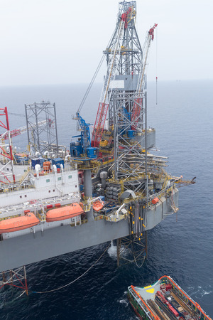 jack up: Aerial View of Offshore Jack Up Drilling Rig and Supply Vessel in The Middle of The Ocean