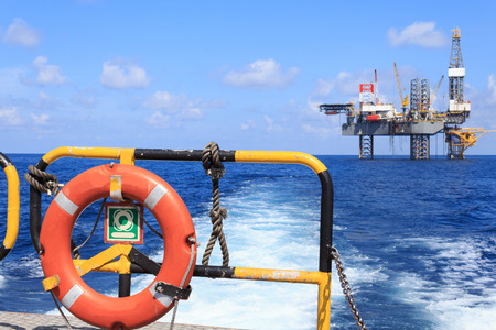 offshore jack up rig: life ring on the offshore supply boat with Jack up drilling rig background Stock Photo