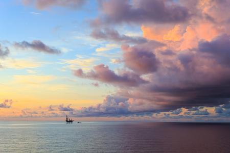 torre de perforacion petrolera: Levantar la plataforma de perforaci�n costa afuera en el medio del oc�ano durante el tiempo de la puesta del sol