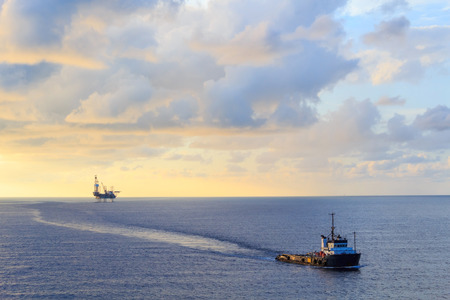 offshore jack up rig: Offshore jack up drilling rig and supply boat in the middle of the ocean during sunset time