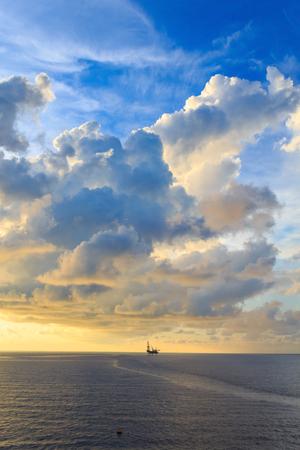 yacimiento petrolero: Levantar la plataforma de perforación costa afuera en el medio del océano durante el tiempo de la puesta del sol