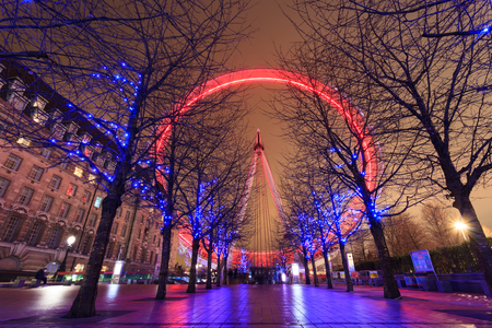 LONDON, UNITED KINGDOM – 24 JANUARY 2016: Long exposure of London Eye with red light and blue lighting decoration on trees. At a height of 135m, it is the tallest Ferris wheel in Europe. Editorial