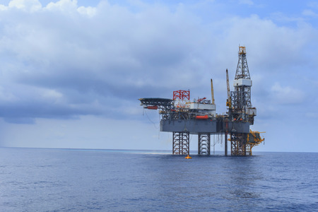 jack up: Offshore Jack Up Drilling Rig Over The Production Platform in The Middle of The Sea on Black and Cloudy Day