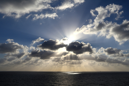 shine: Light rays shine through the group of clouds Stock Photo