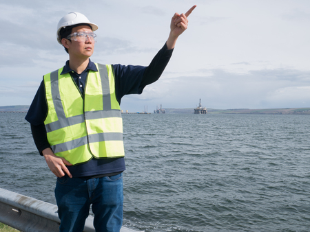 technician: An asian engineer pointing and standing in front of semi submersible oil rig Stock Photo
