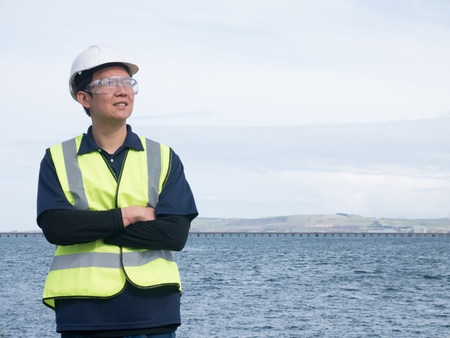 contruction: An asian engineer standing in front of the long bridge across the ocean Stock Photo